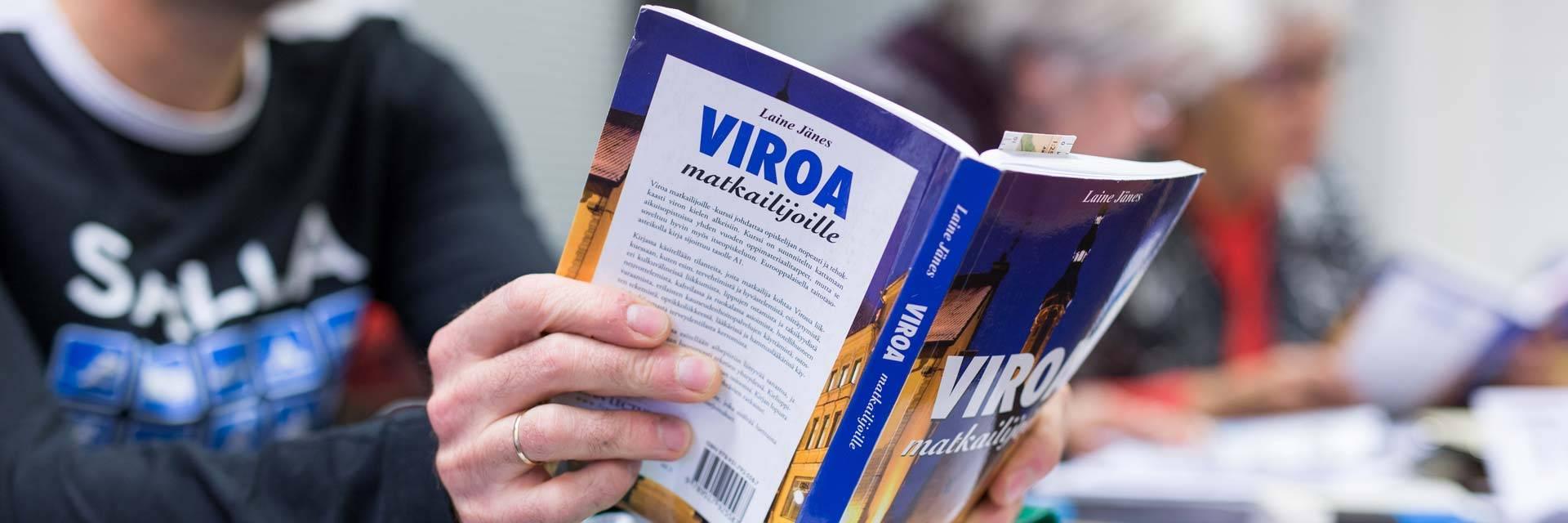 Henkilö opiskelemassa Viron kieltä kirjasta.