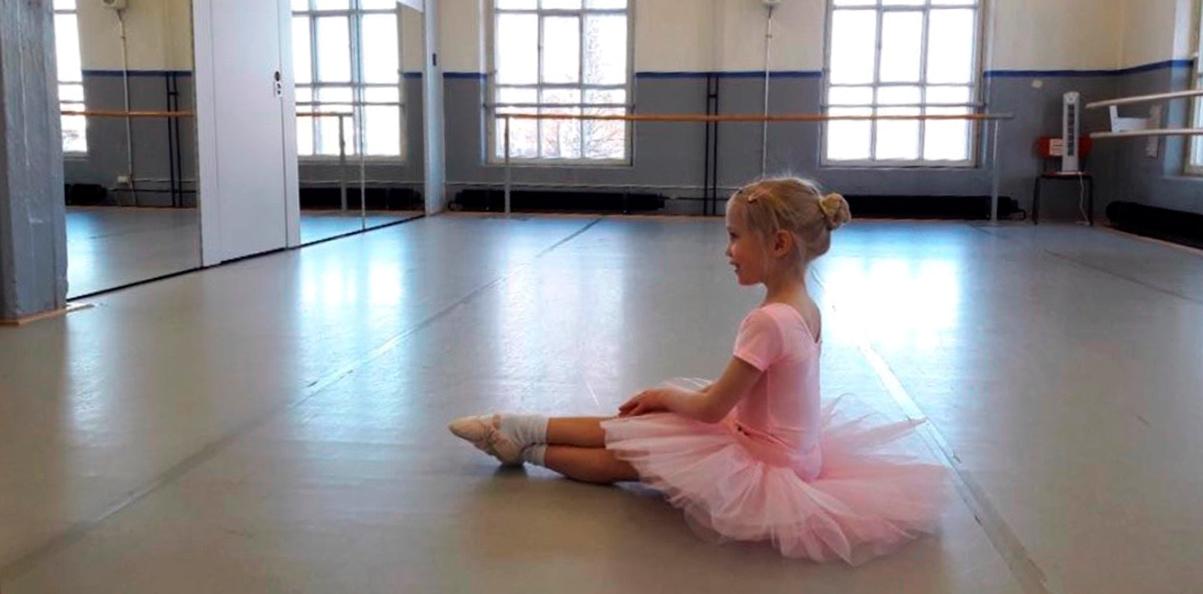 Tyttö istuu balettipuvussa tanssiopiston salin lattialla.