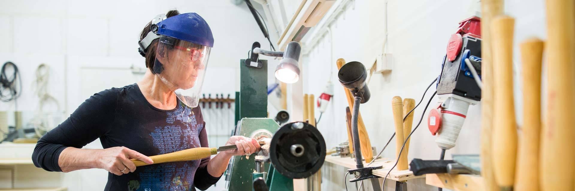 Nainen tekee puutöitä Valkeakoskiopiston kurssilla