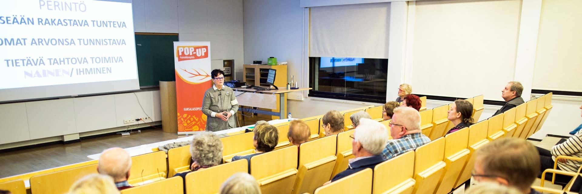 Luennoitsija ja yleisöä Valkeakoski-opiston luentosalissa