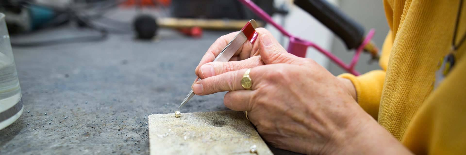 Nainen valmistaa korua Valkeakoskiopiston korunvalmistuskurssilla